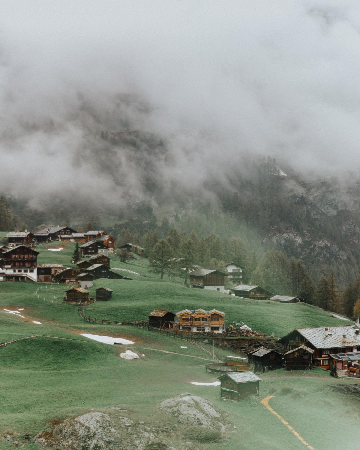 Byn Zermatt bland molnen i Schweiziska alperna