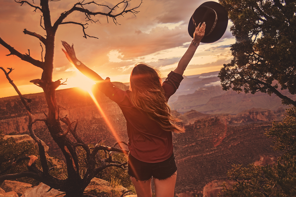 Woman with hands in the air in Grand Canyon sunset / Solnedgång i Mather Point