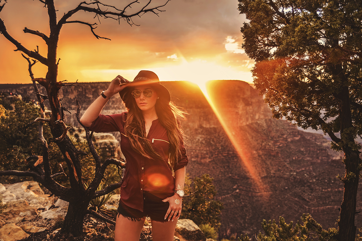 Girl with Ray-Bans and hat standing in Grand Canyon sunset at Mather Point