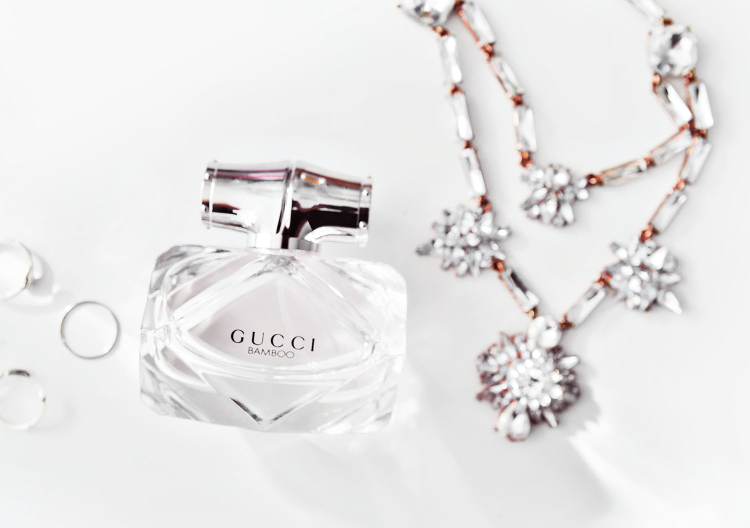 Flatlay with Gucci Bamboo Eau de Toilette & crystal necklace