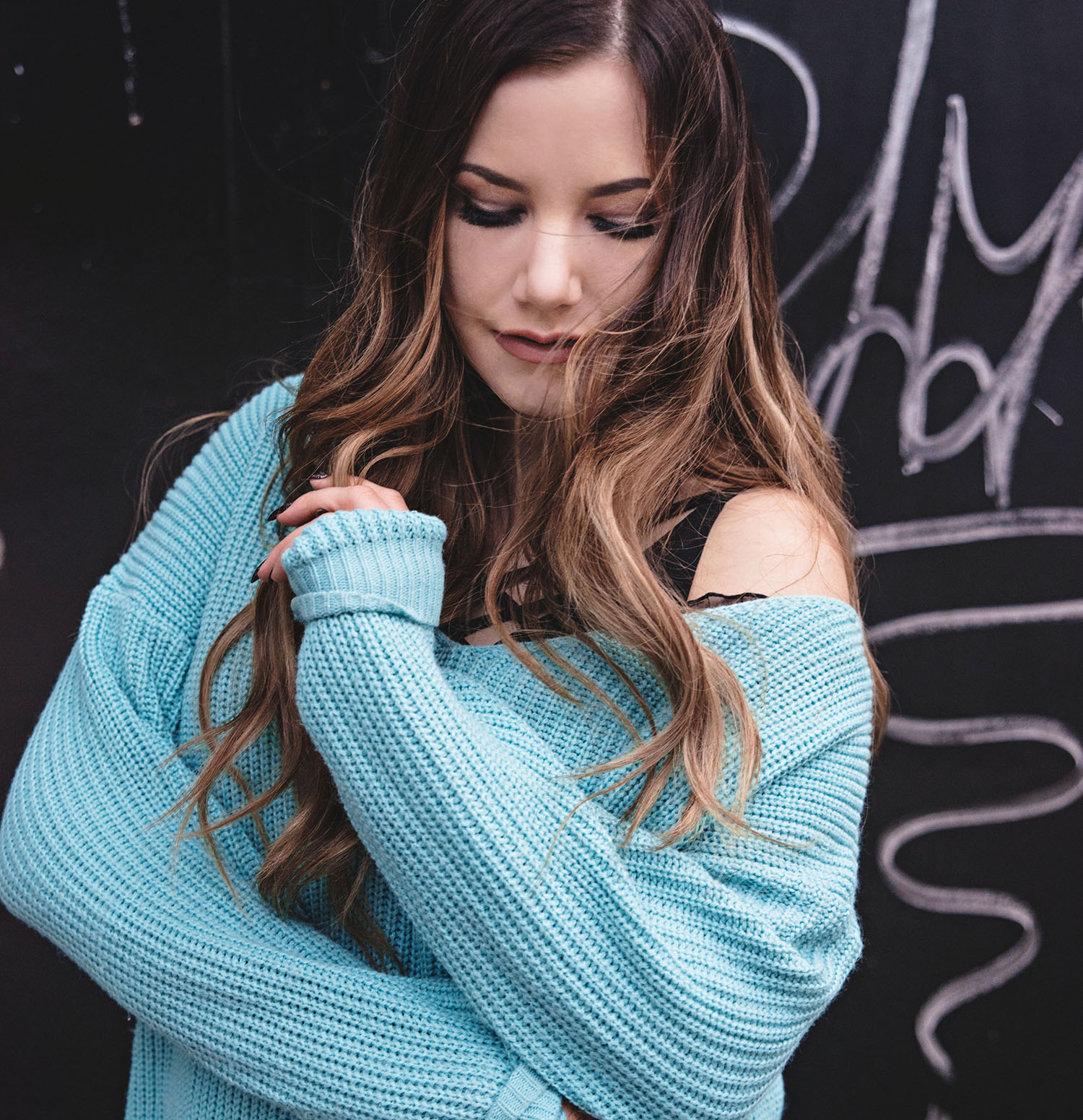 Woman with balayage hair and beach waves +wearing cosy mint green knitted sweater