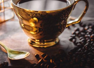 Coffe beans and a golden cup of coffee in candle light - The Nescafé Plan