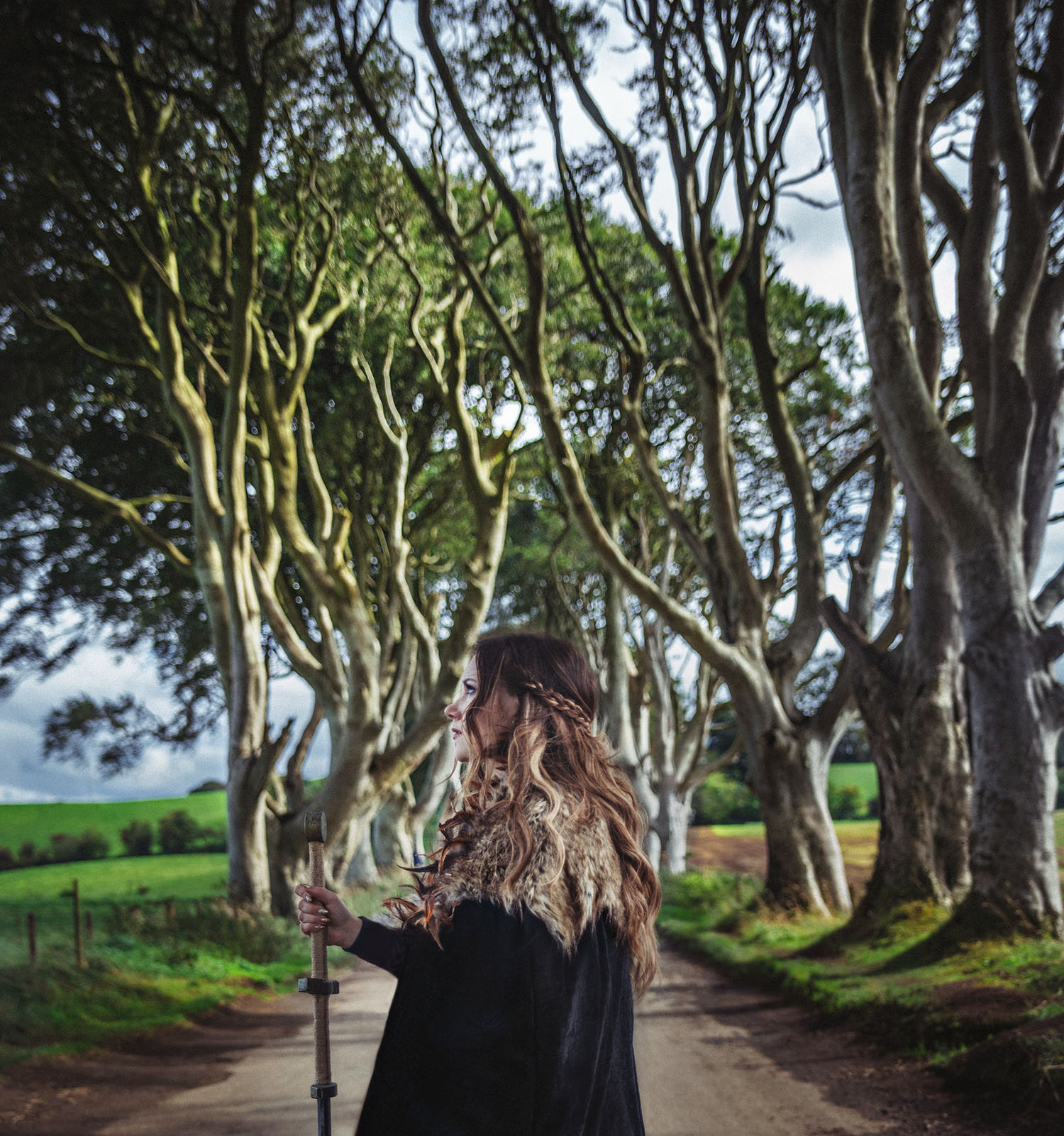 Woman with cape and sword standing under The Dark Hedges in Northern Ireland