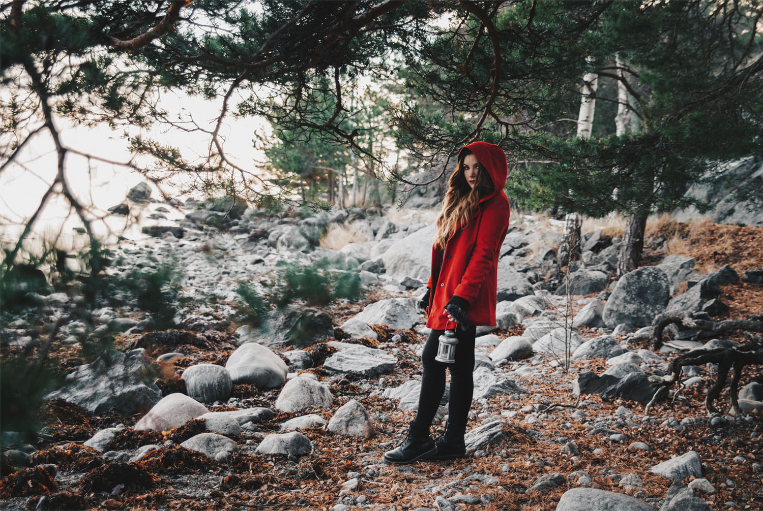 Little Red Riding Hood Fashion Story: Young woman in red cape with lantern in the woods