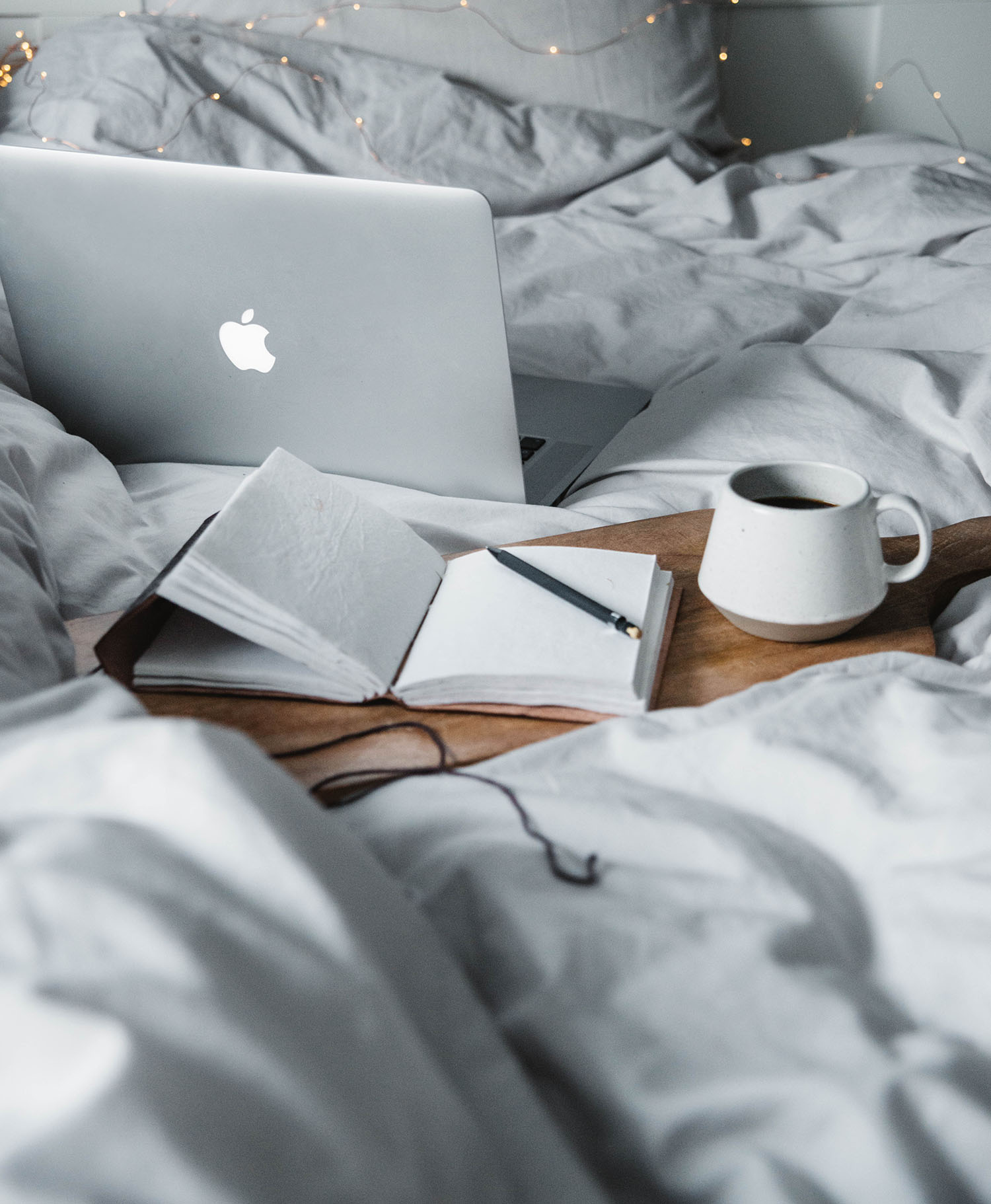 Cutting board, coffee cup and Macbook in a bed with grey sheets