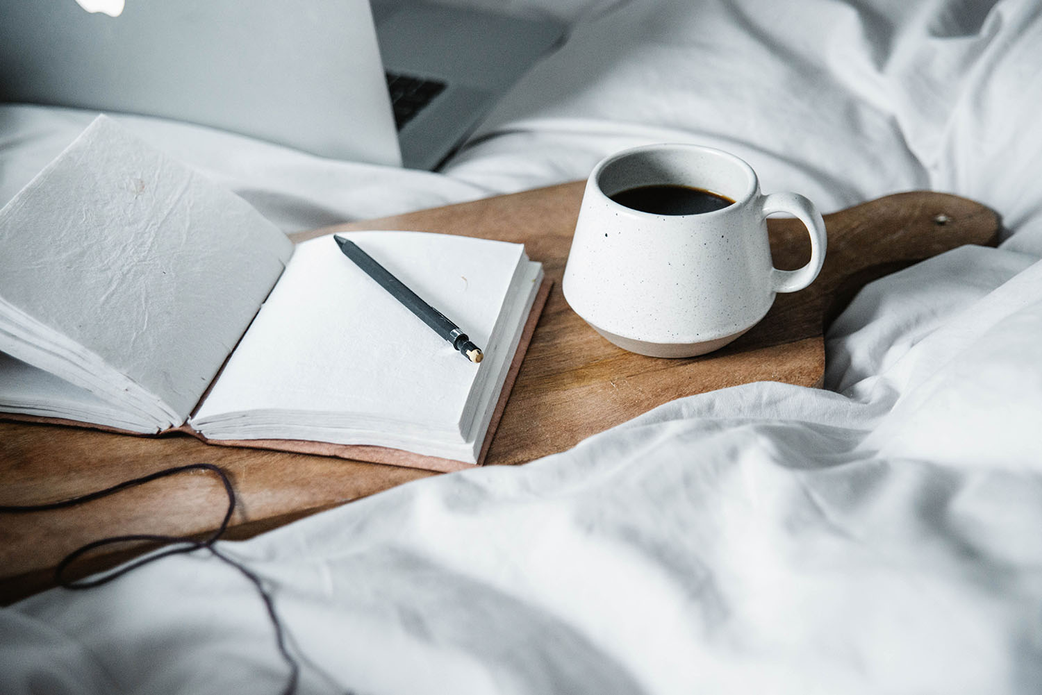 Cutting board, coffee cup, notes and Macbook in a bed with grey sheets