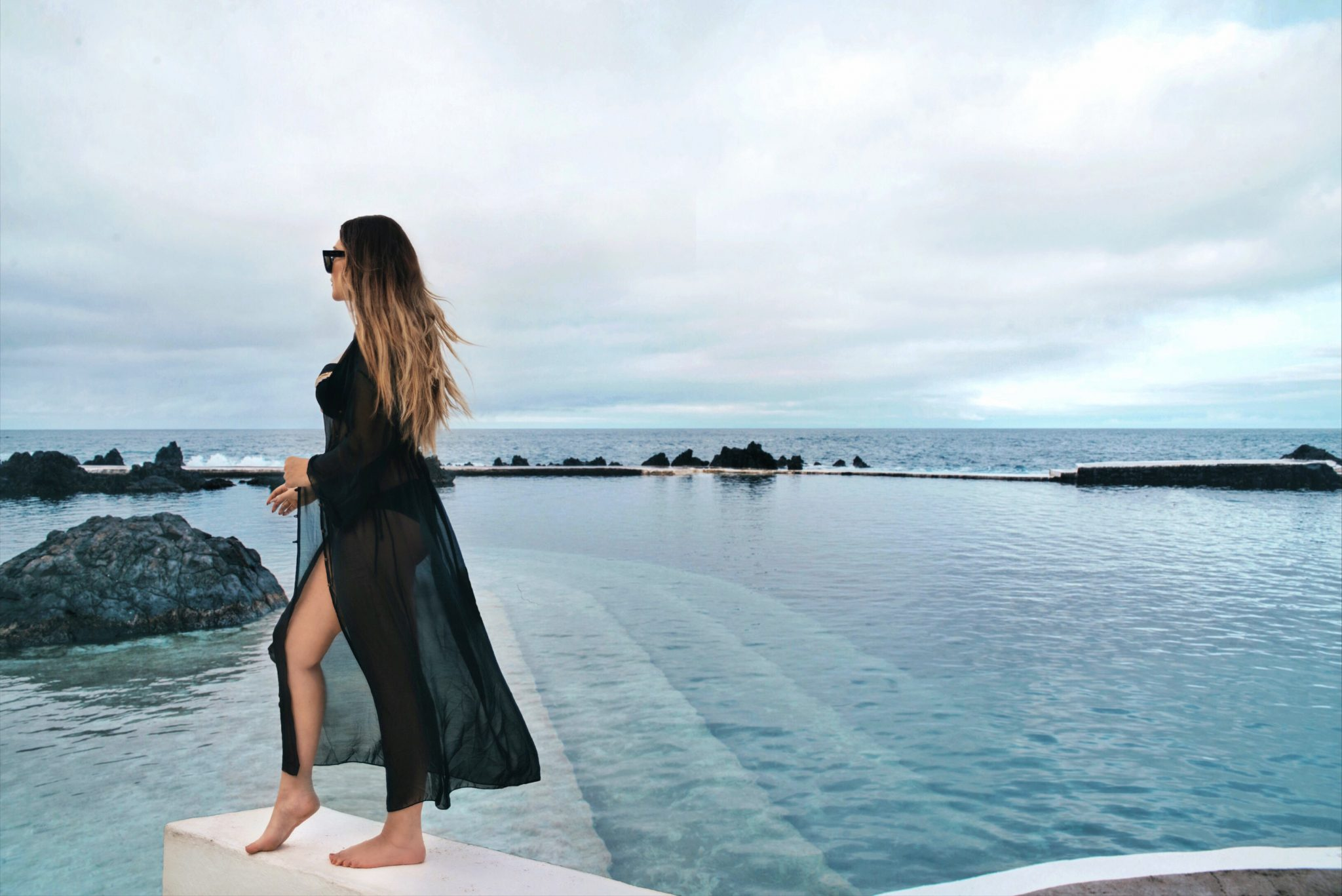 Woman with bikini and black kimono standing in front of natural swimming pools in Madeira