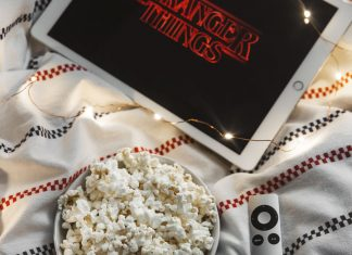 iPad Pro with Stranger Things on Netflix in bed with popcorn
