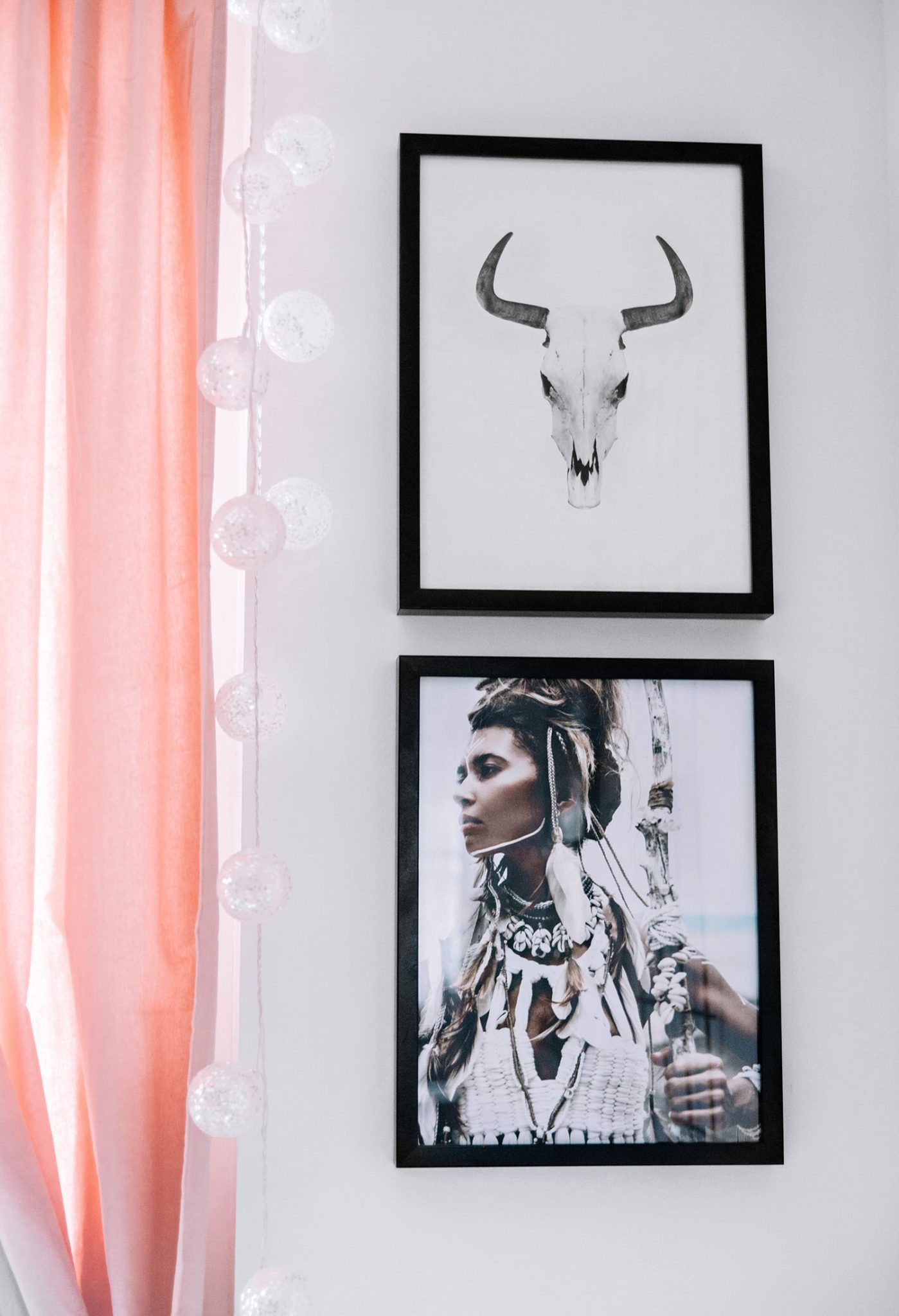 Two boho posters hanging next to window with pink curtains