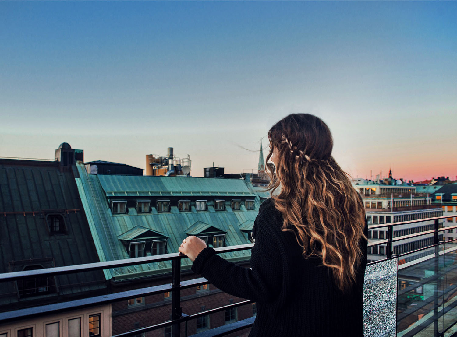 Woman standing looking out over Stockholm city with faux waterfall braid and beach waves