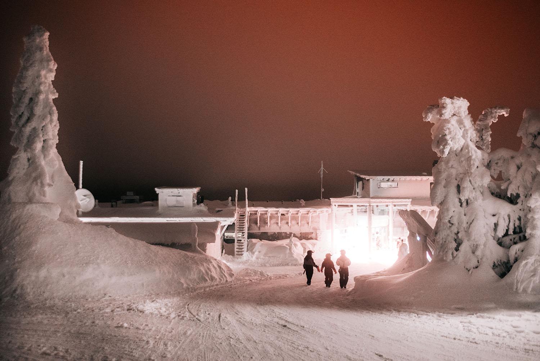 Three people walking toward light in the Finnish winter wonderland Iso-Syöte