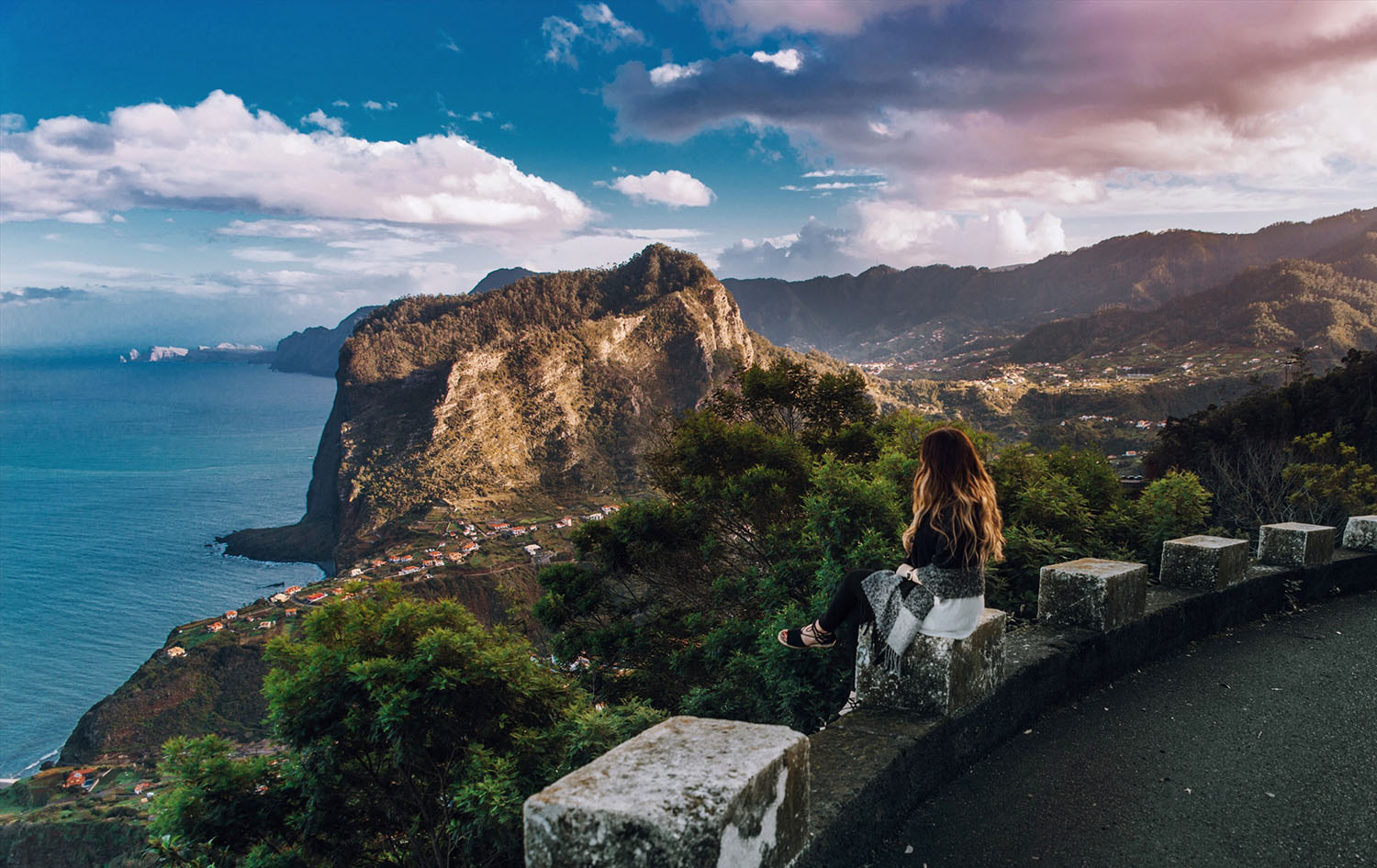 Woman sitting on edge looking out over Madeira's Beautiful Landscape