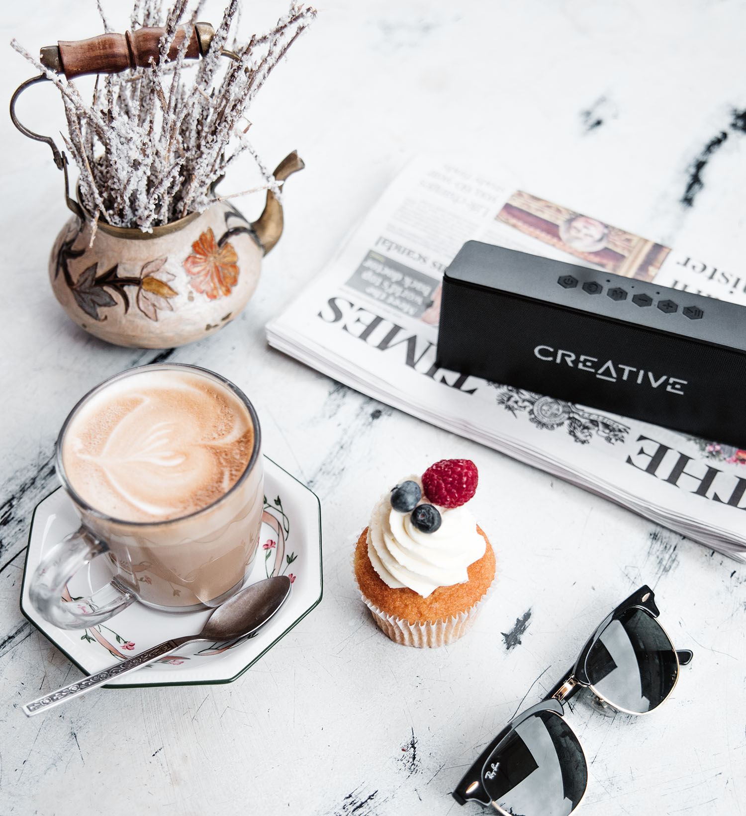 Flatlay with Creative MUVO 2 Bluetooth Speaker, Latte, Ray-Ban & Cupcake