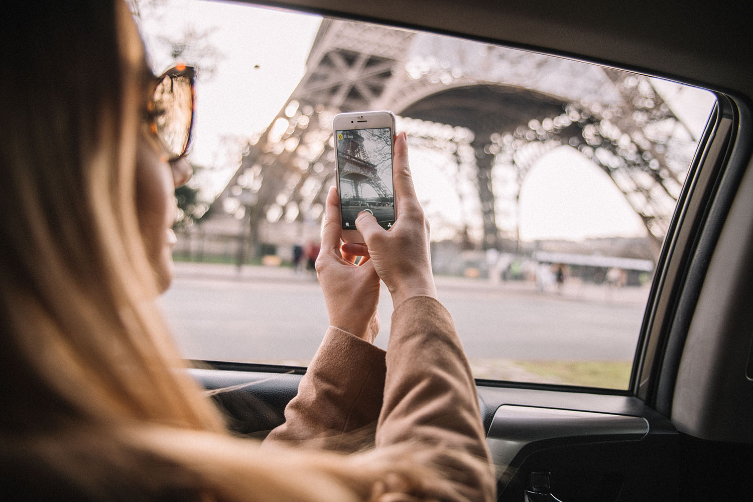 Woman with iPhone taking photo of The Eiffel Tower in Paris