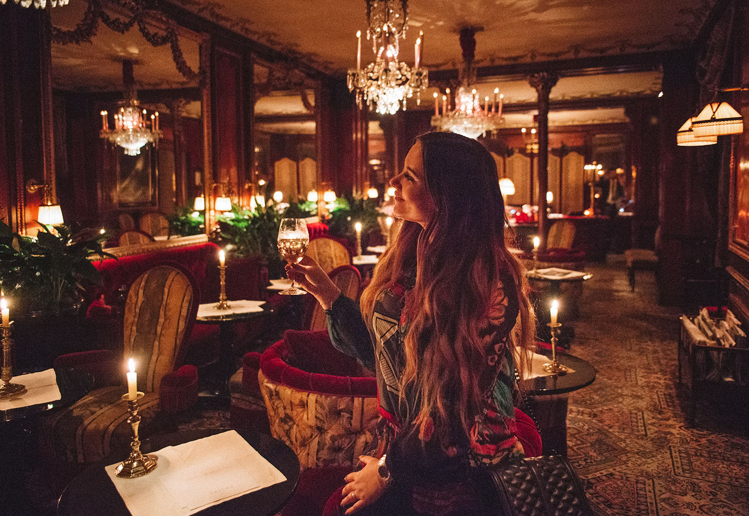 Woman with long hair in beautiful room with a glass of wine at Hotel Costes in Paris