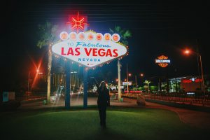 Woman standing in front of Welcome to Fabulous Las Vegas Sign at night