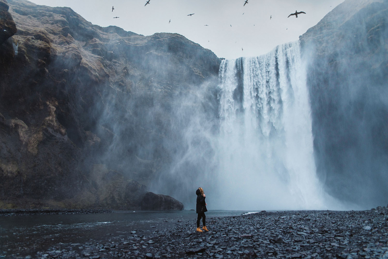 Girl standing in front of Skógafoss Waterfall in Iceland