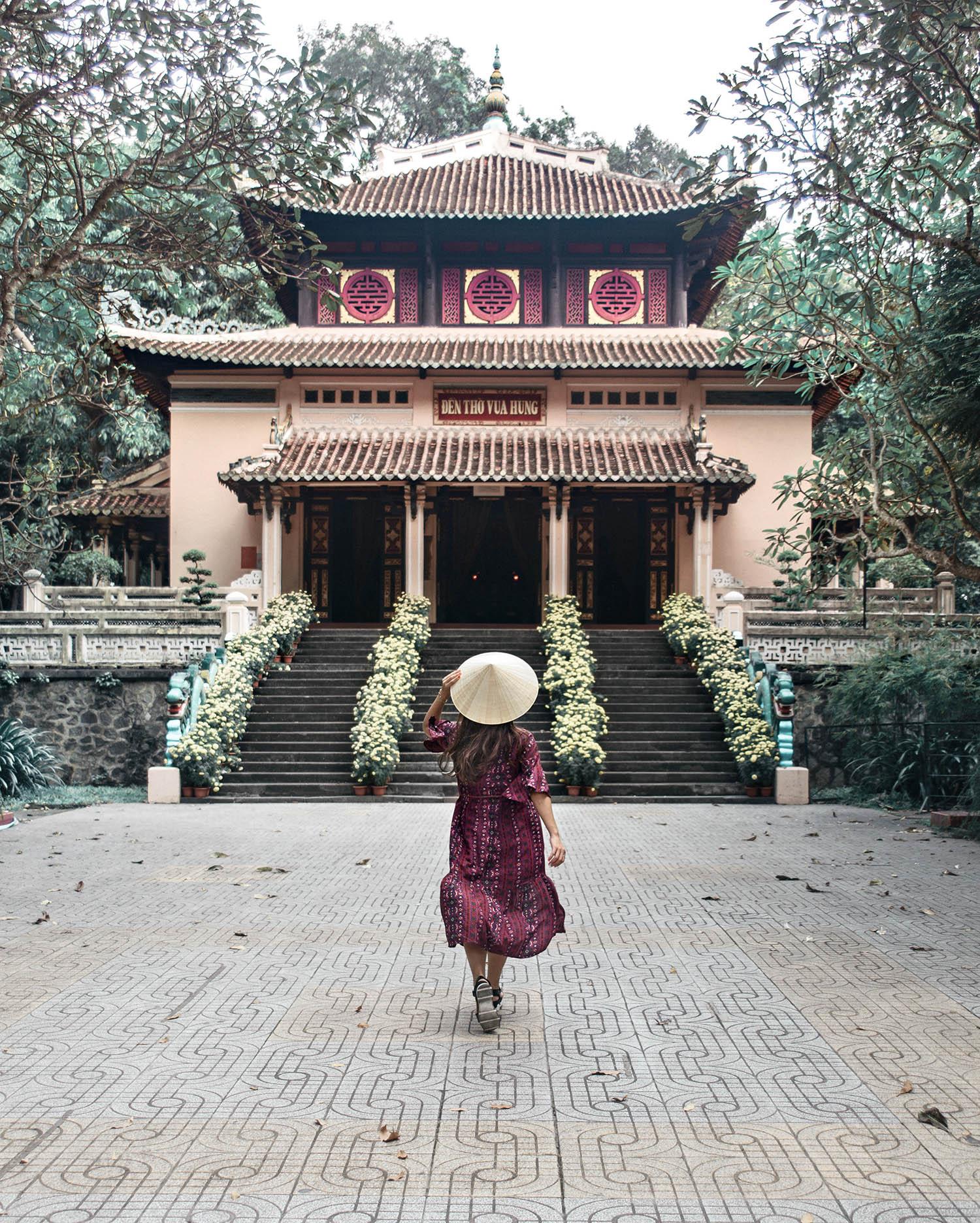Girl with conical hat walking towards Đền Thờ Vua Hùng - Buddhist temple in Ho Chi Minh City, Vietnam