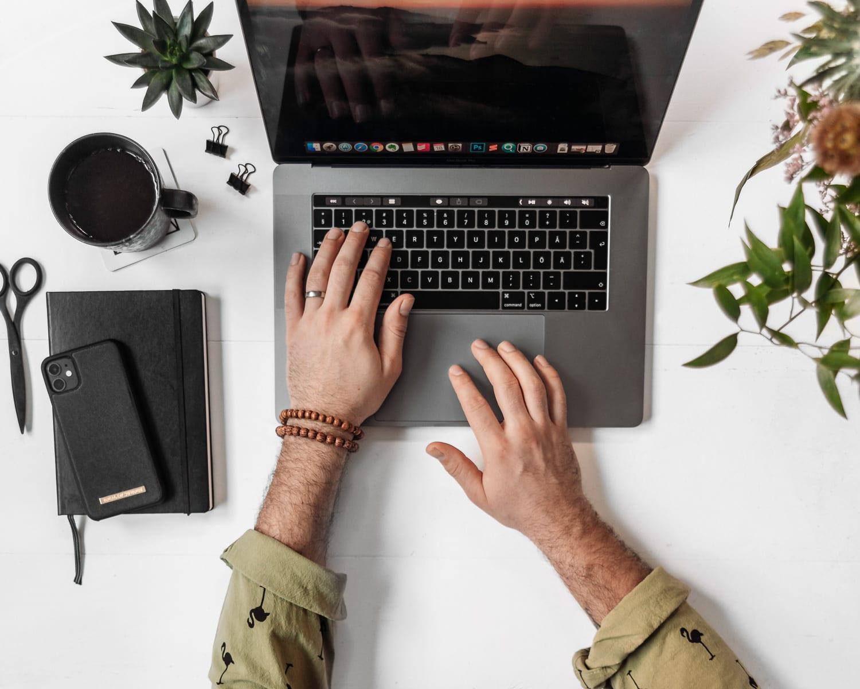 Jobba hemifrån: Man som jobbar på en Macbook Pro Laptop