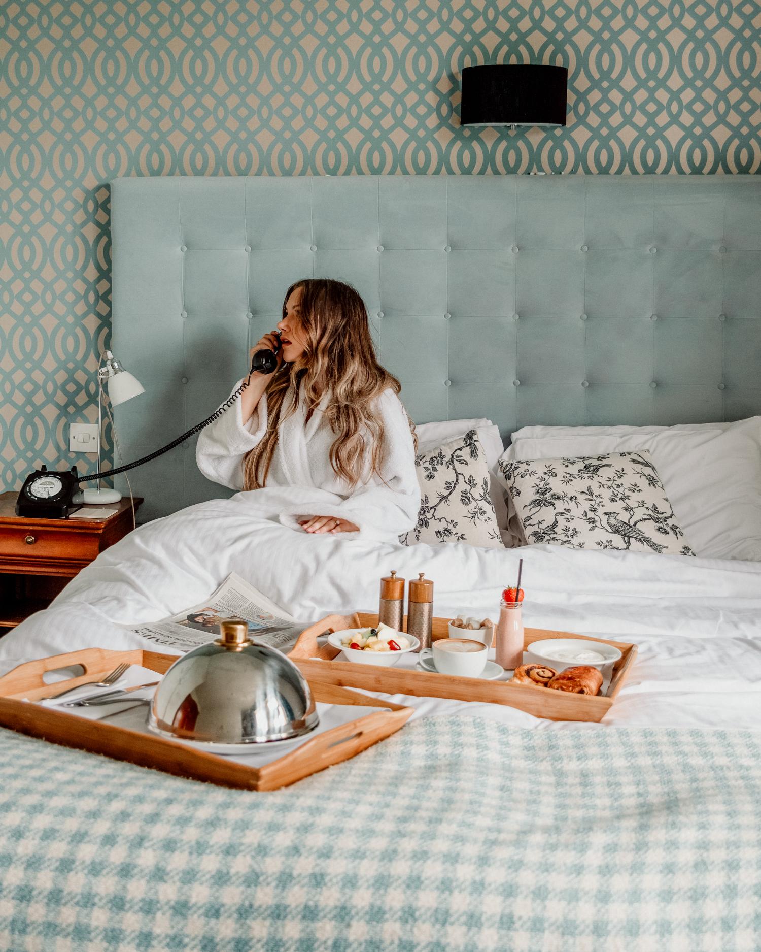 Kvinna i badrock som pratar i telefon i sängen på The Alverton Hotel i Cornwall, Storbritannien