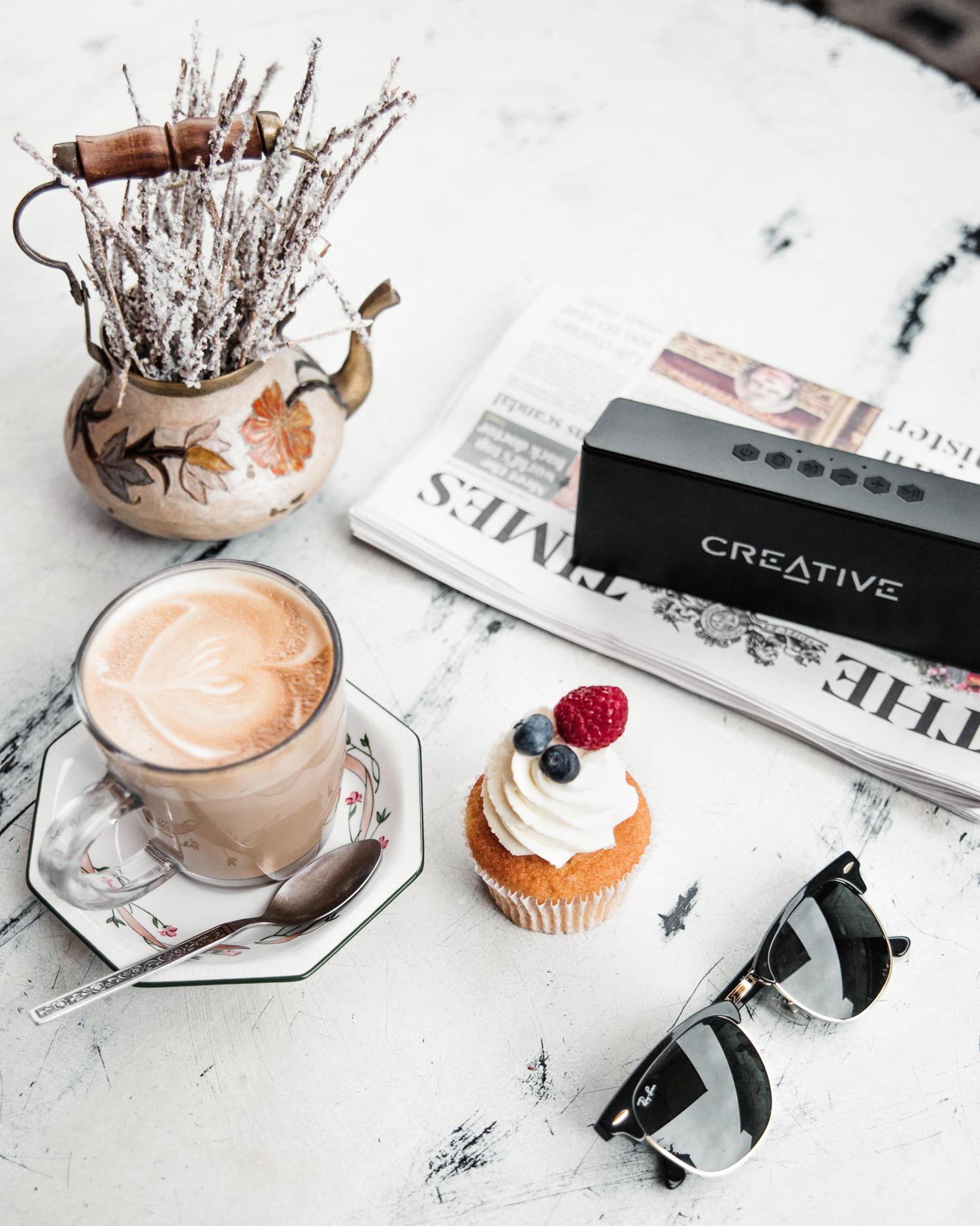 Flatlay med kaffe, bakverk, tidning och högtalare från Creative