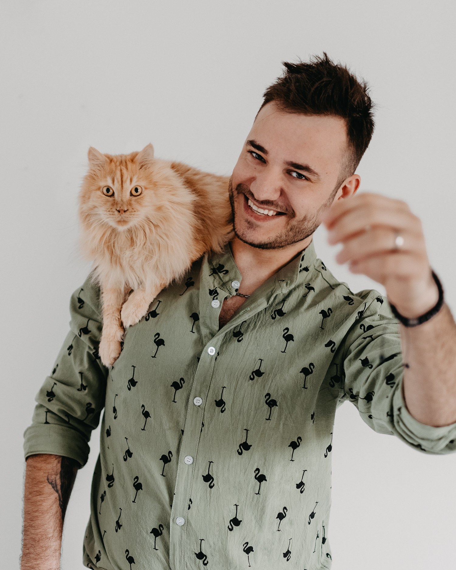 Cute furry orange cat sitting on man's shoulder