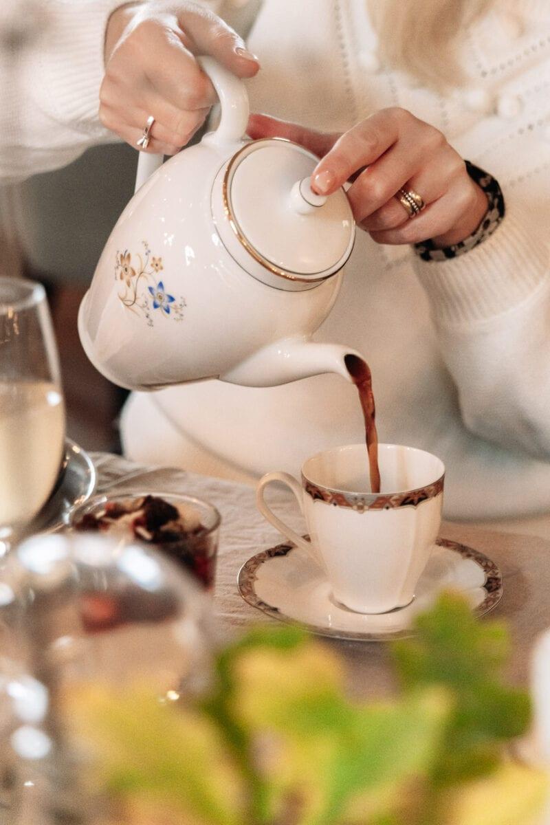 Kvinna häller upp en kopp kaffe på elegant restaurang