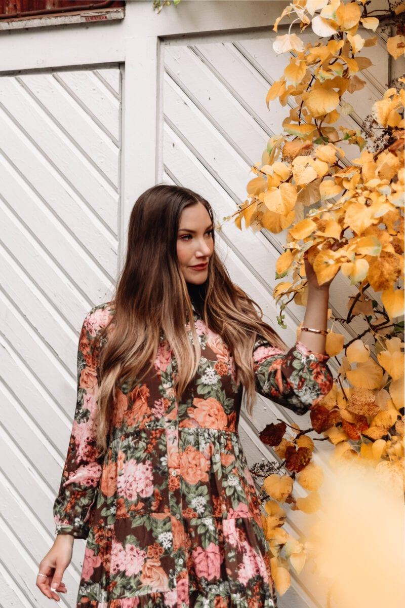 Ida Josefin Eriksson bland gula höstlöv, iklädd en blommig maxiklänning från Ajlajk