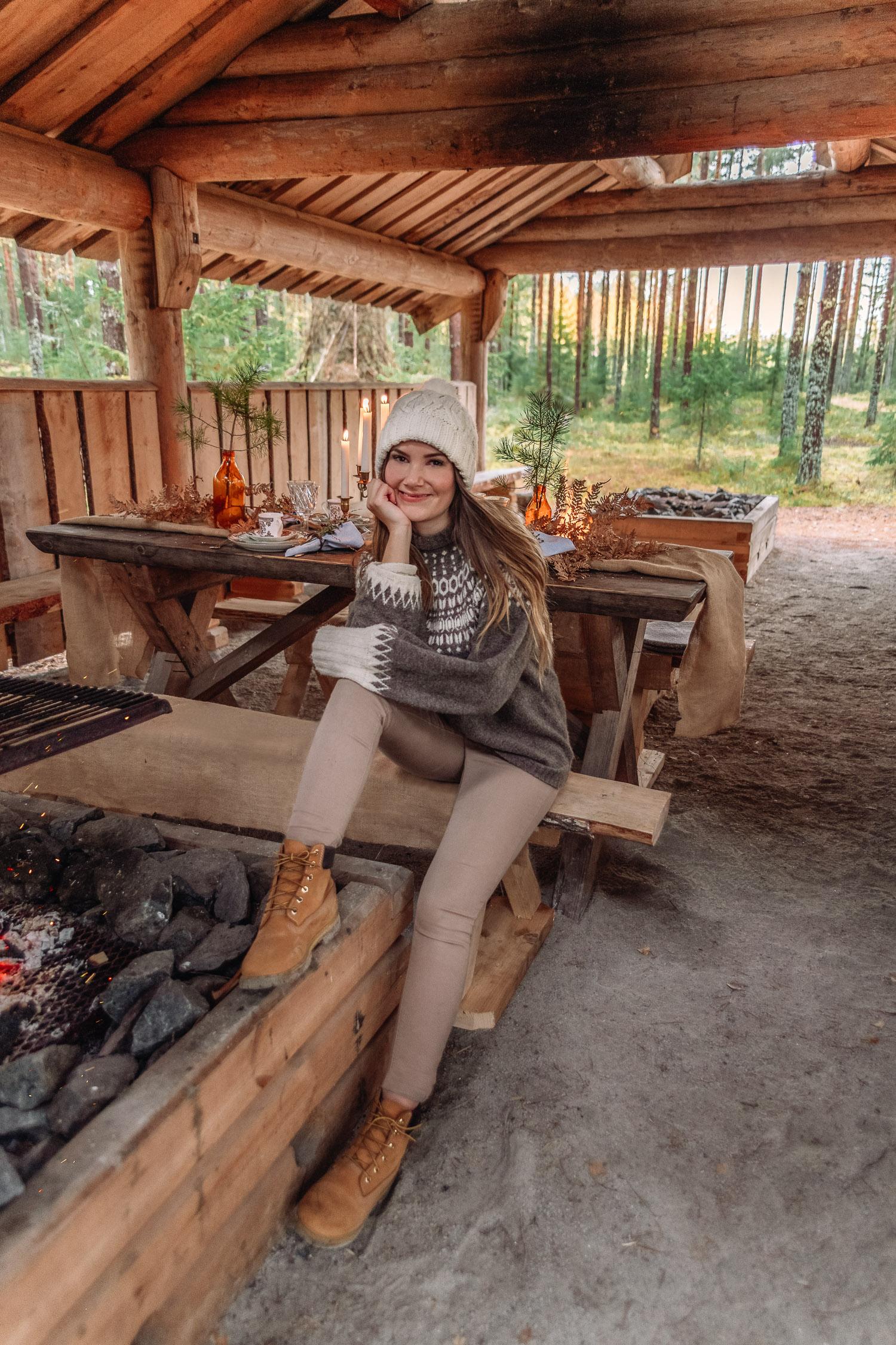 Ida Josefin Eriksson i mysig isländsk stickad tröja, mössa och Timberlands vid brasa och uppdukad utomhuslunch i Brevens Bruk i Örebro