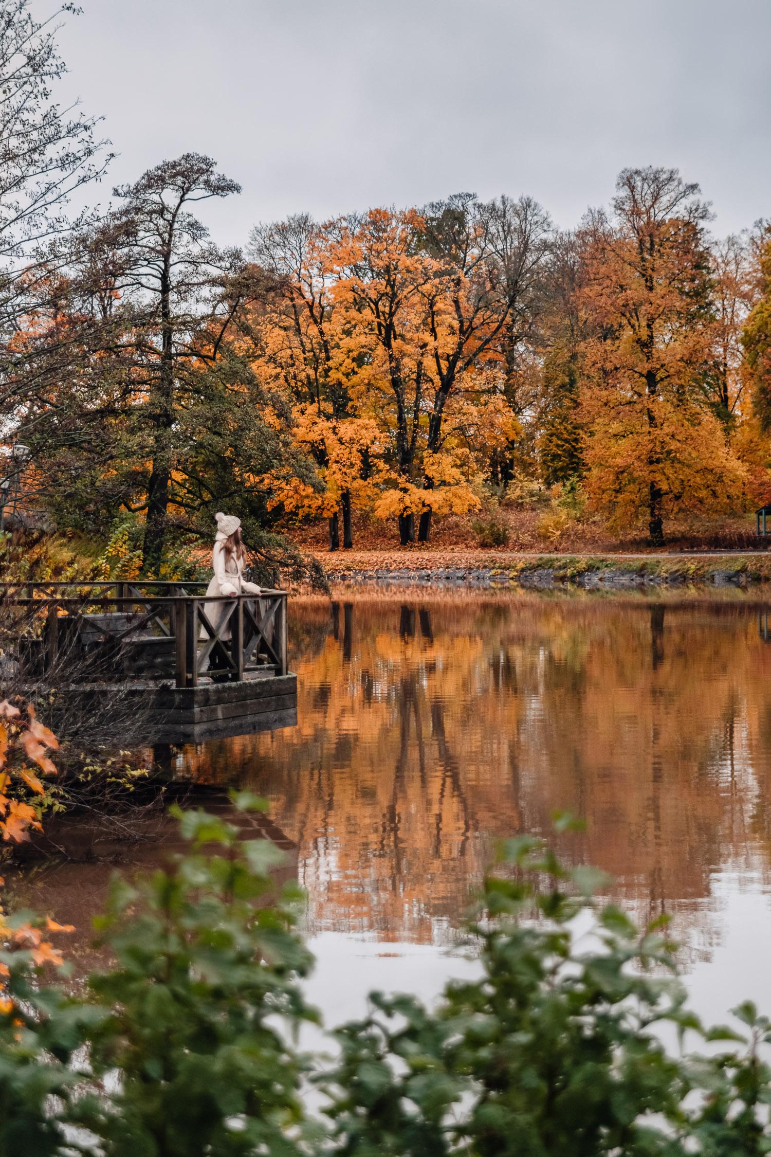 Ida Josefin Eriksson står i vit kappa och mössa på en brygga på spegelblanka Åstråket vid Svartån i Örebro - omringad av orangea höstlöv