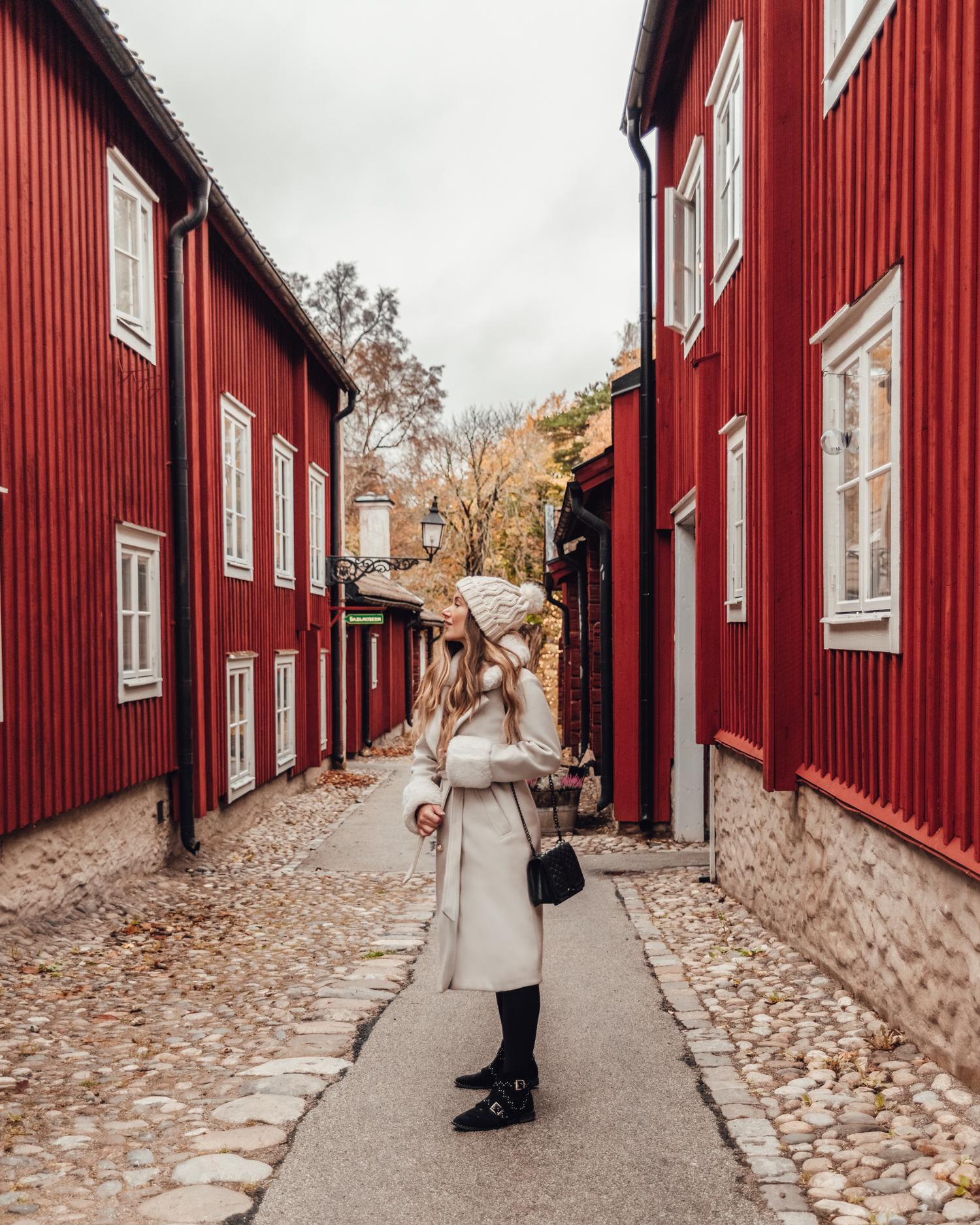 Ida Eriksson i vit fuskpälskappa på en gata bland röda trähus i Wadköping friluftsmuseum, Örebro