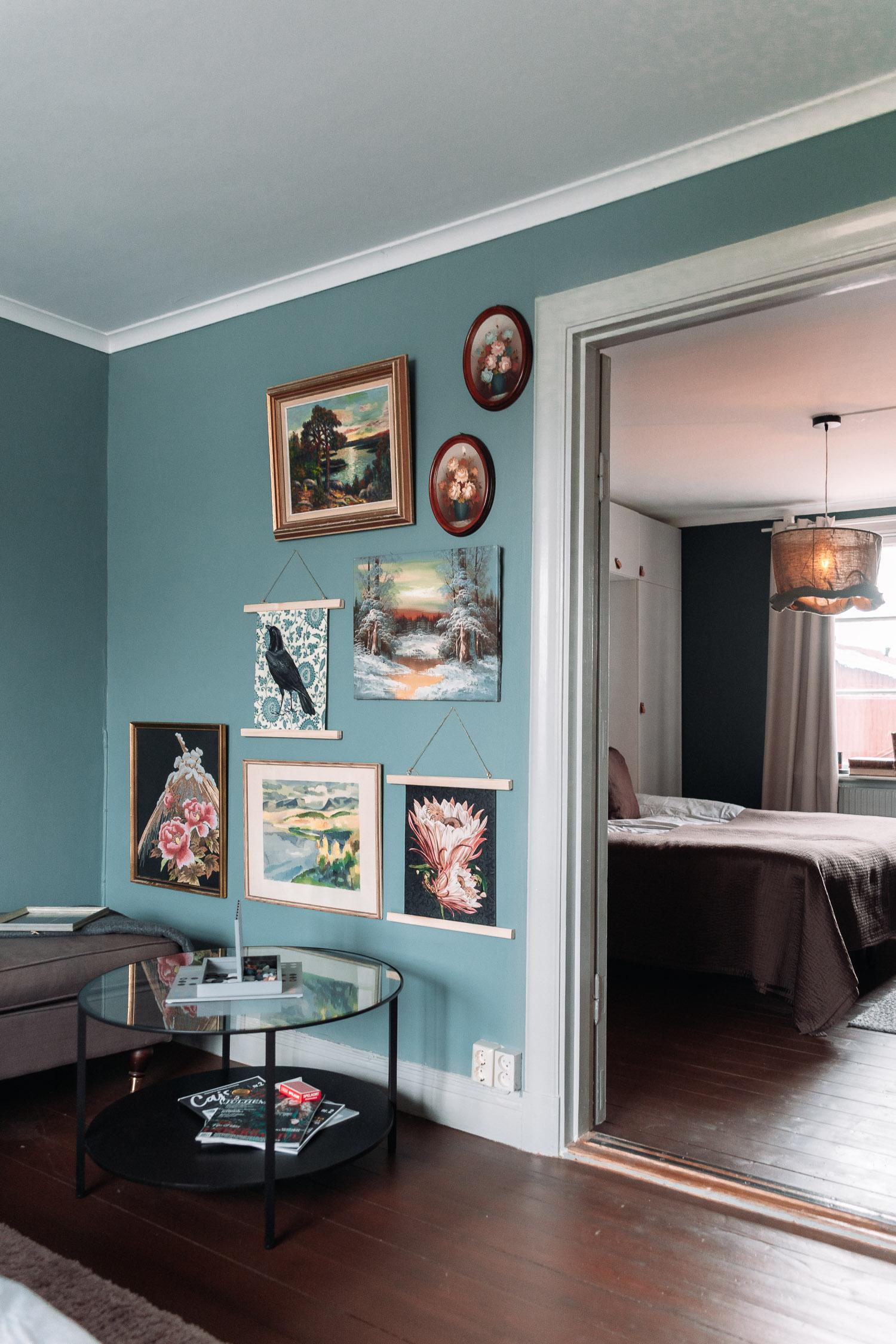 Charmig inredning med blågön vägg och second hand-tavlor i olika storlekar på Egastronomis boende i Kumla, Örebro