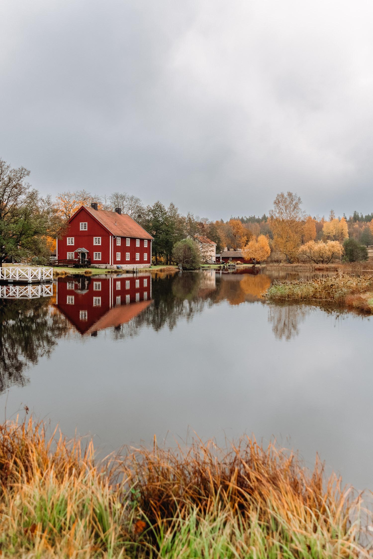 Rött trähus med vita knutar och färgglada höstträd speglas i vattnet i Brevens Bruk, Örebro