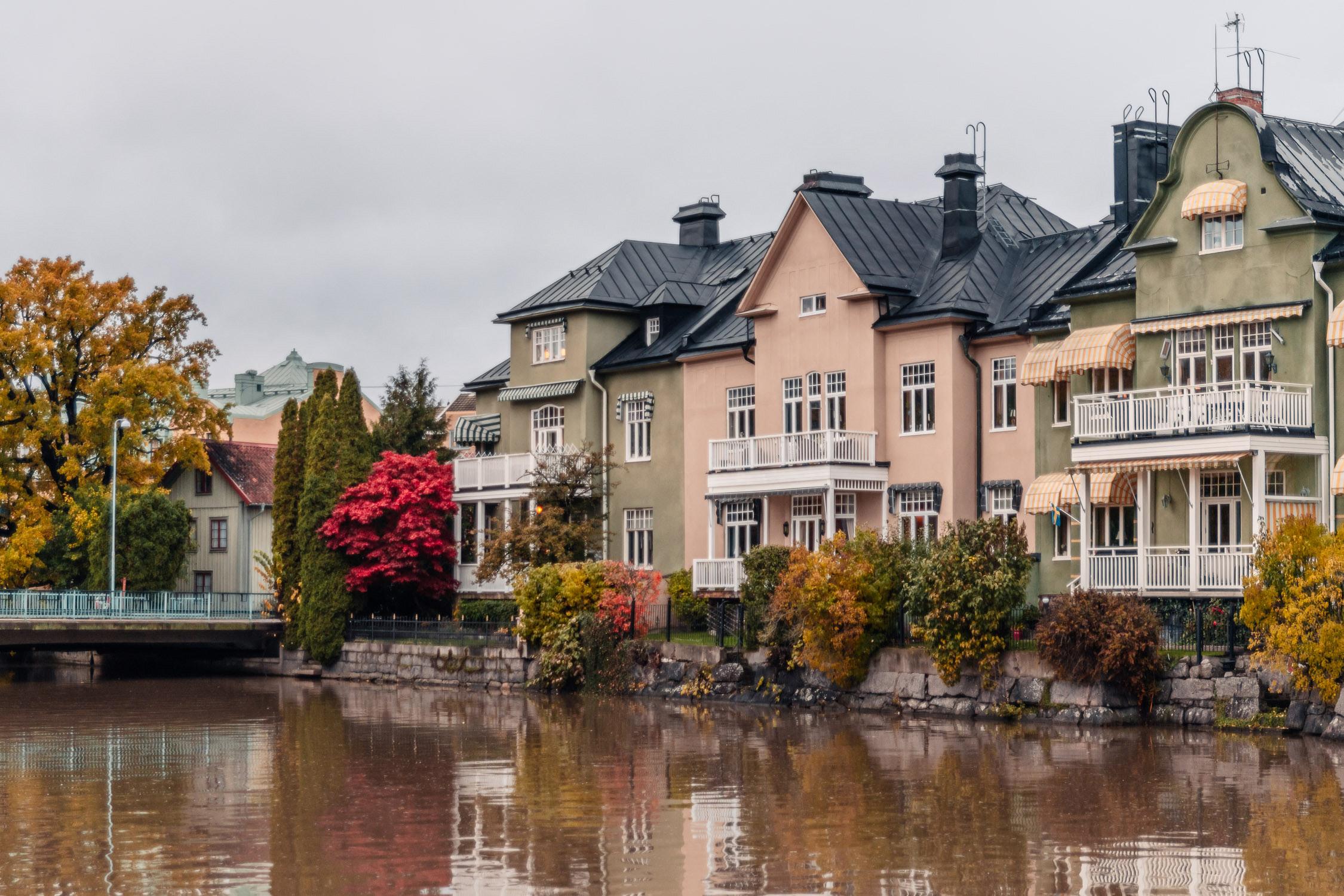 Vackra hus i grönt och rosa vid Åstråket längs Svartån i Örebro