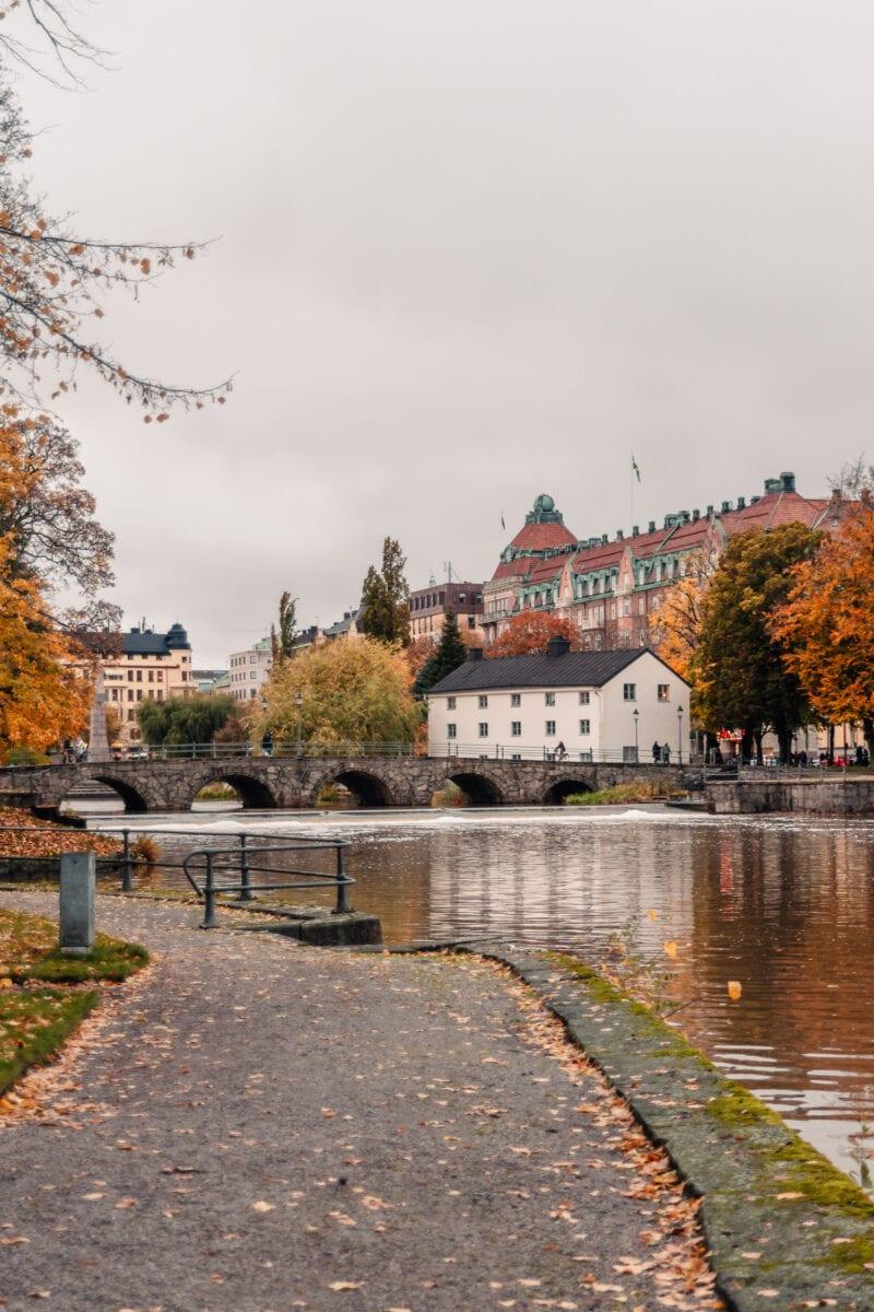 Färgglada träd och stiliga byggnader vid Svartån i stadsparken