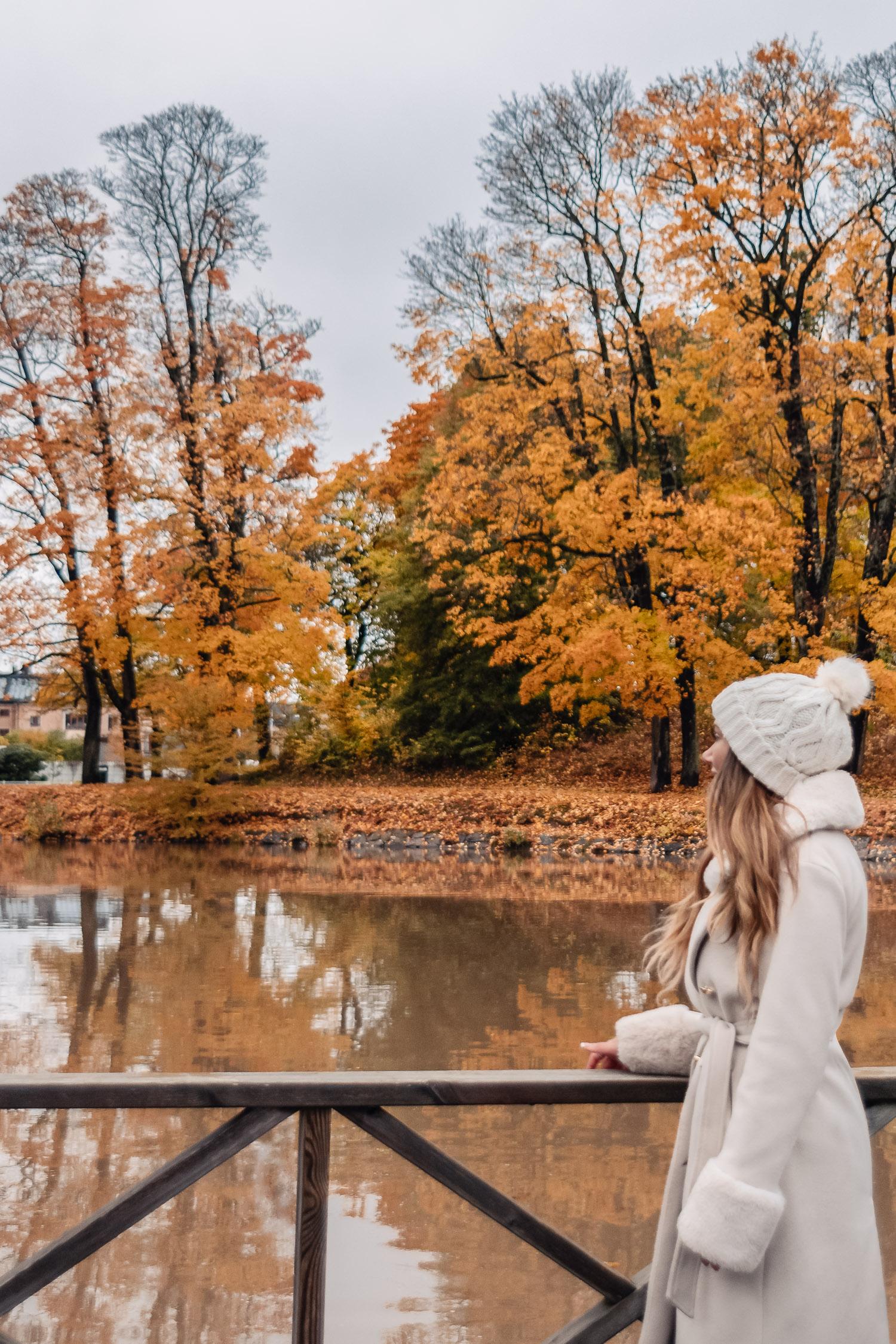 Ida Josefin Eriksson står i vit kappa med fuskpälsdetaljer och blickar ut över spegelblank vy med orangea höstlöv längs Åstråket vid Svartån i Örebro