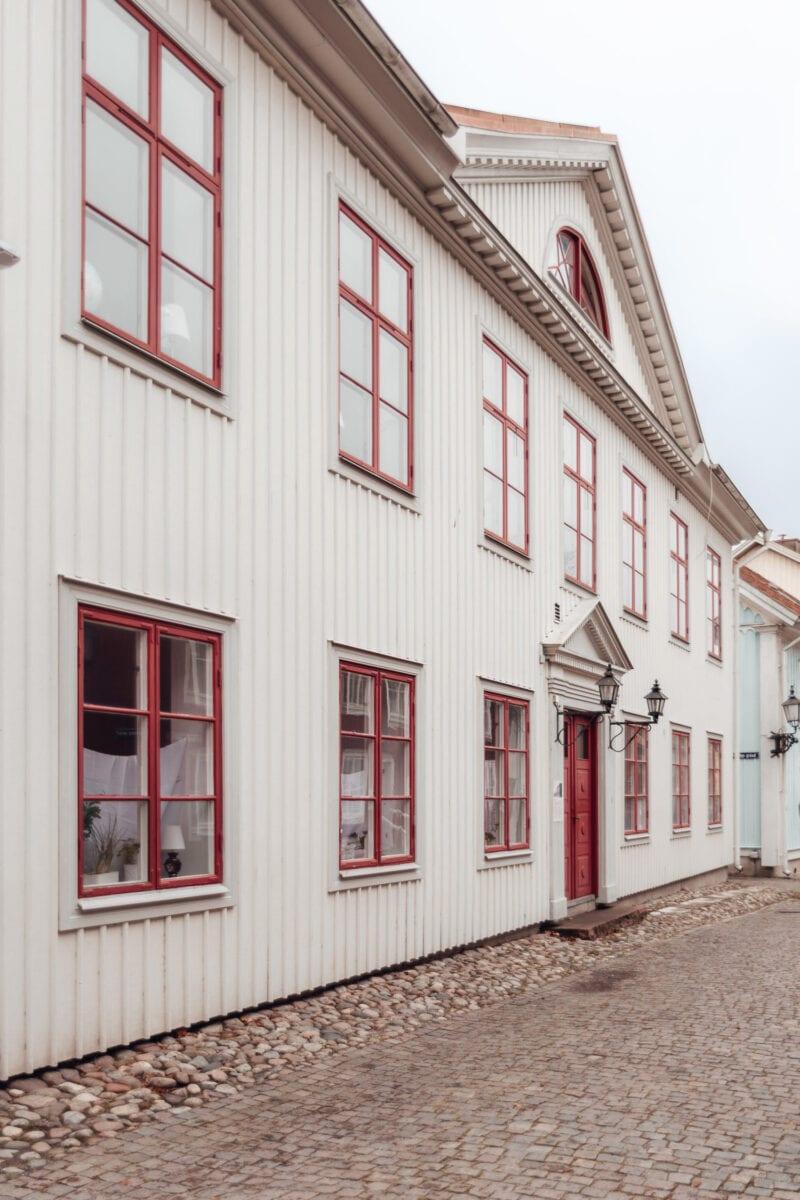 Vacker vit byggnad med röda fönsterbågar i Wadköping, Örebro
