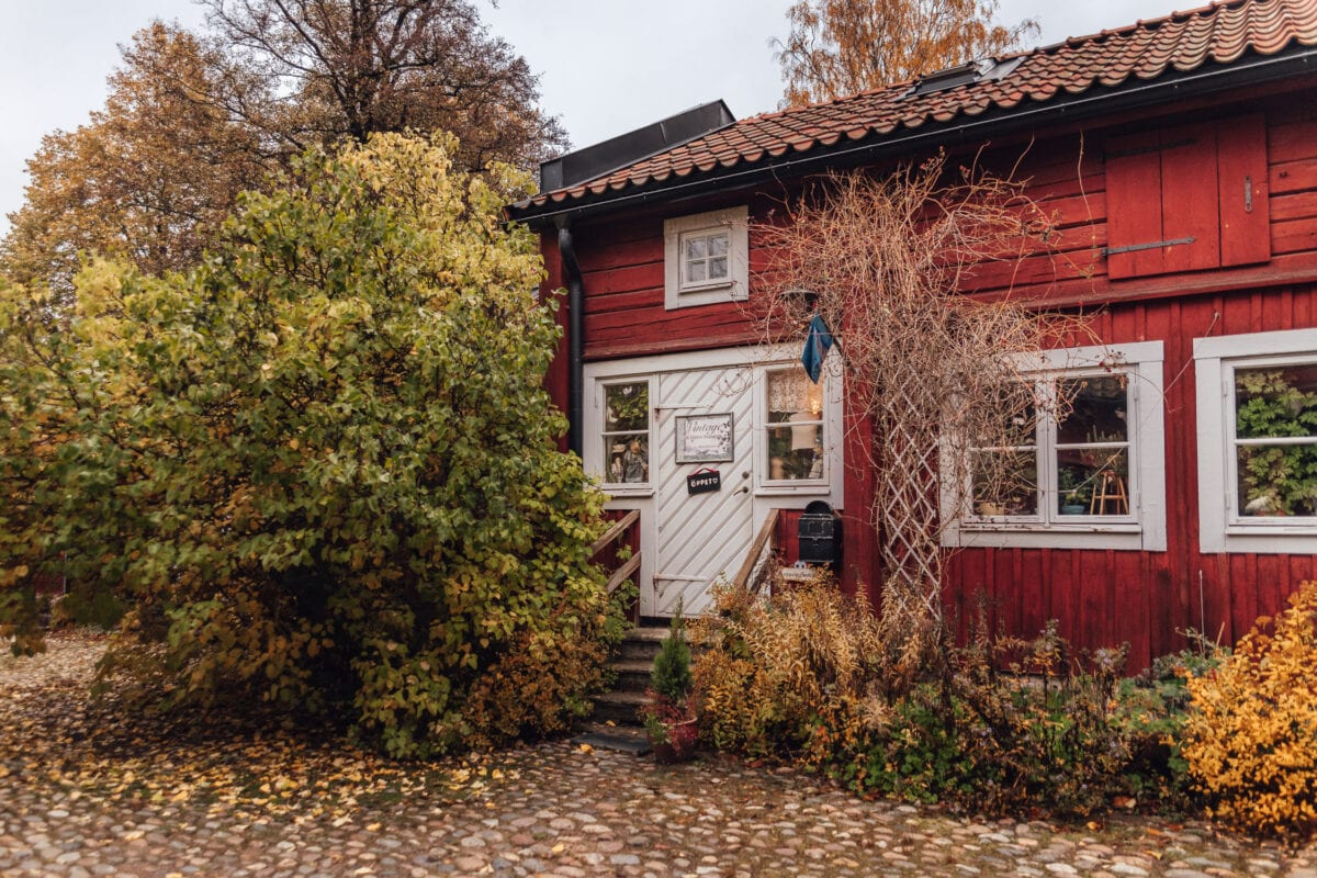 Vintage second hand i rött trähus omgivet av färgglada höstlöv i Wadköping, Örebro