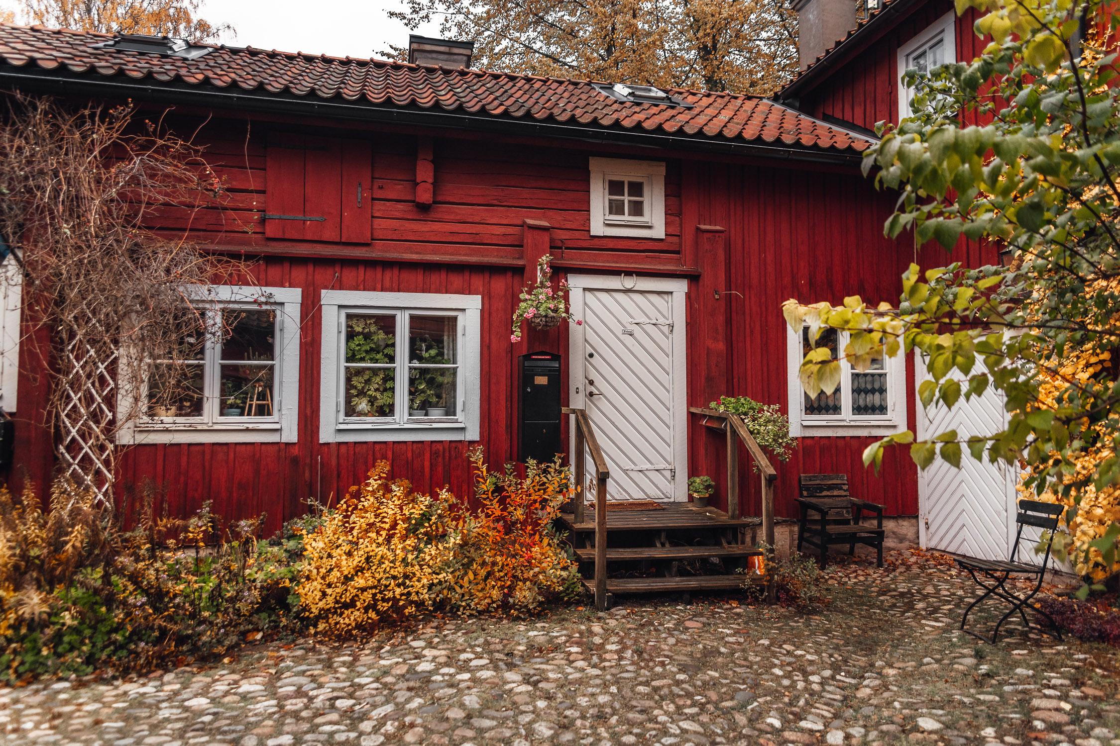 Rött trähus omringat av färgglada höstlöv i Wadköping friluftmuseum i Örebro